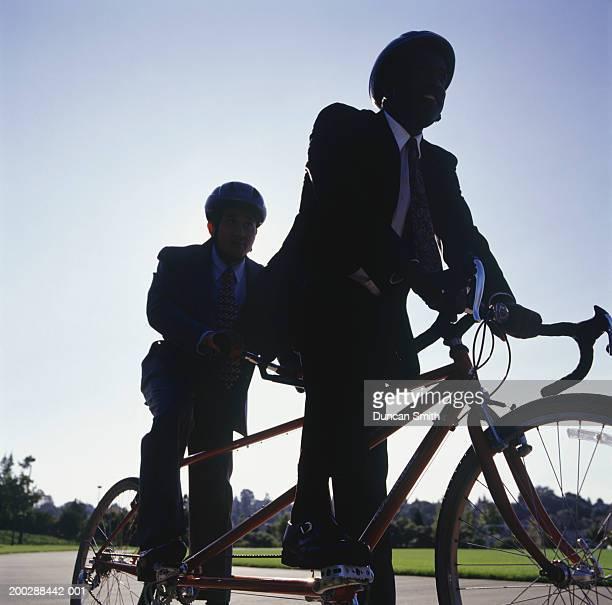 Businessmen sitting on tandem bicycle on path, low angle view