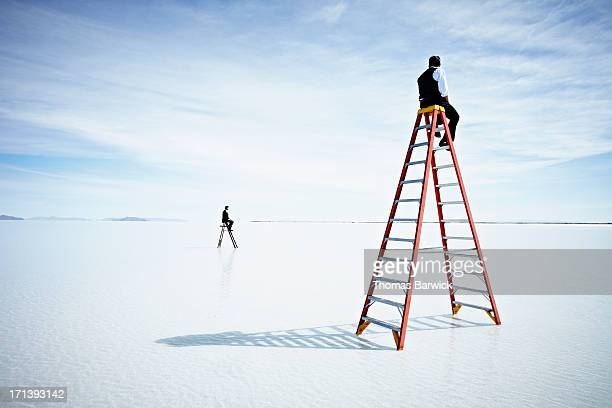 Businessmen sitting on two different sized ladders
