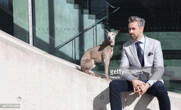 Businessmen sitting with dog on retaining wall in city