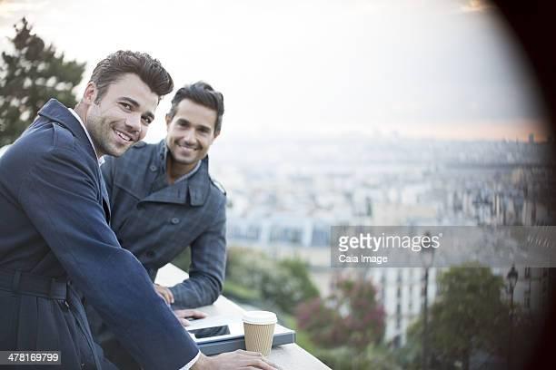 Businessmen smiling at railing overlooking Paris, France