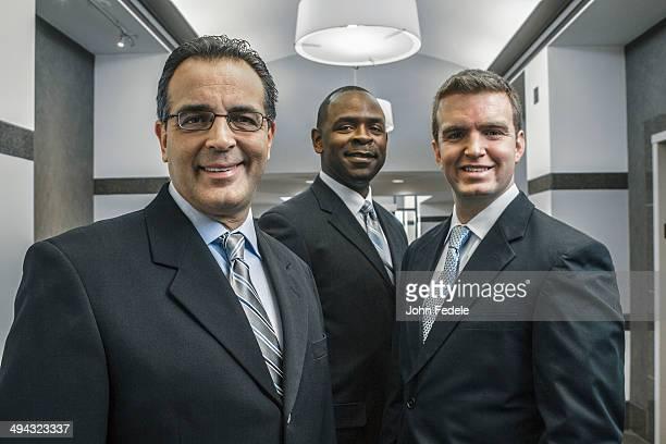 Businessmen smiling in office corridor