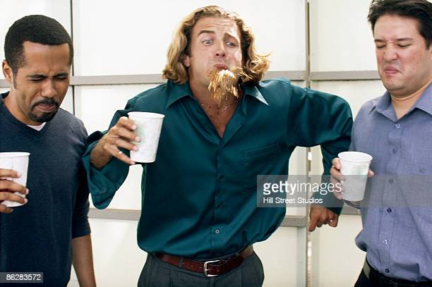 Businessmen spitting out disgusting coffee