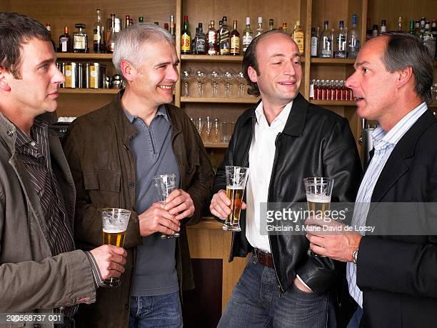 Businessmen standing at bar, holding beer glass, smiling