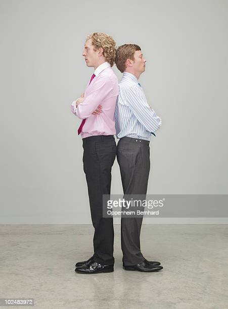 businessmen standing back to back