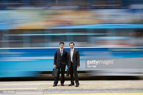 Businessmen standing by blurred bus