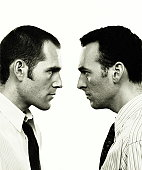 Businessmen standing face-to-face (B&W)