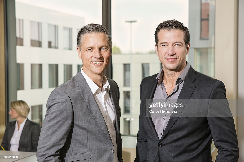 Businessmen standing in conference room : Stock Photo