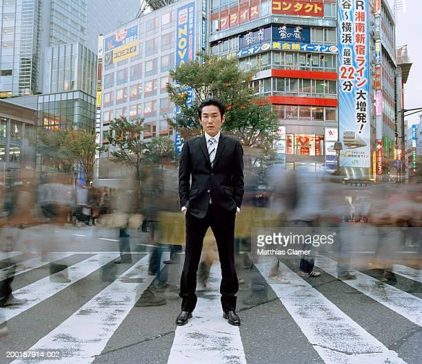 Businessmen standing in crosswalk (long exposure)
