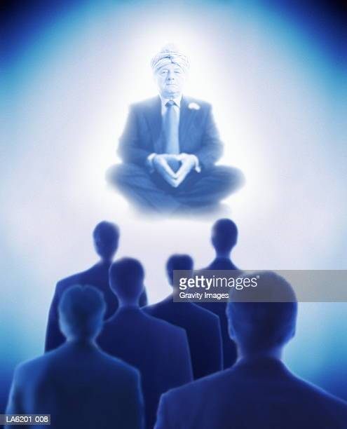 Businessmen standing in front of 'genie' businessman (Composite)