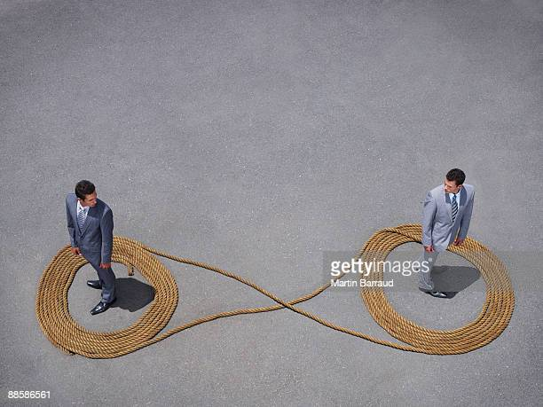 Businessmen standing in rope infinity symbol