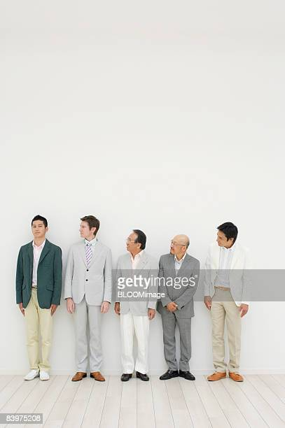 Businessmen standing in row against wall, looking at man at far left