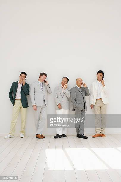 Businessmen standing in row against wall, talking on cellular phone