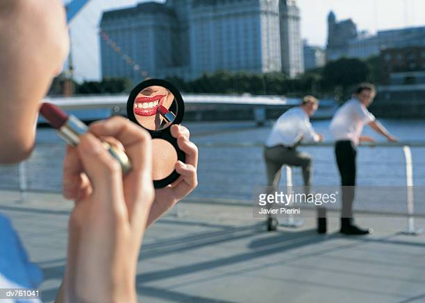 Businessmen Standing in the Background Staring at a Businesswoman Applying Lipstick in a Hand Mirror