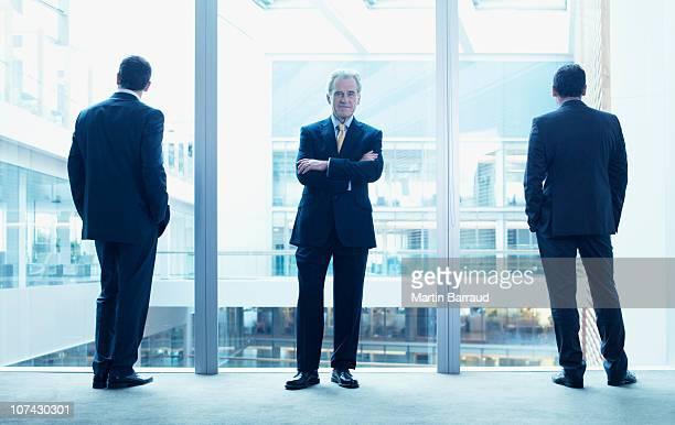 Hommes d'affaires debout près de mur de verre dans le bureau