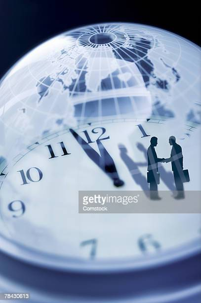 Businessmen standing on clock inside globe