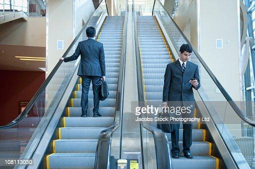Businessmen standing on escalators