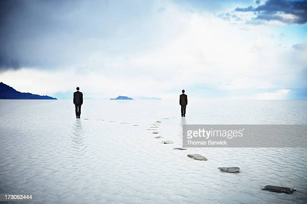 Businessmen standing on forked pathway in water