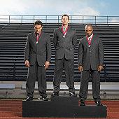 businessmen standing on podium wearing medals around neck