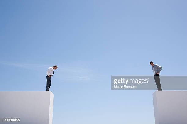Businessmen standing on wall looking down