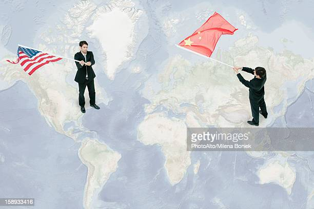 Businessmen standing on world map, waving American and Chinese flags