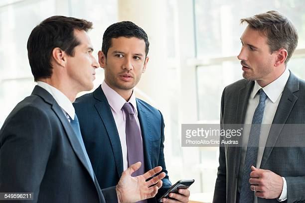 Businessmen standing together having serious discussion