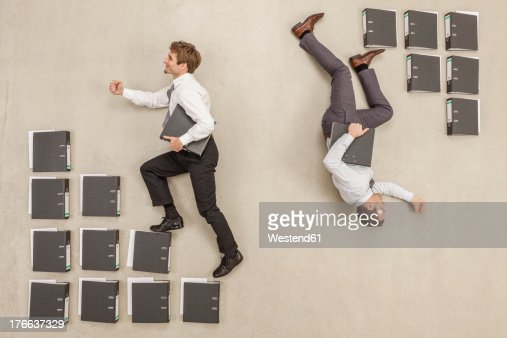 Businessmen stepping on files in opposite direction