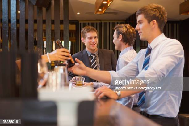 Businessmen talking and drinking at bar