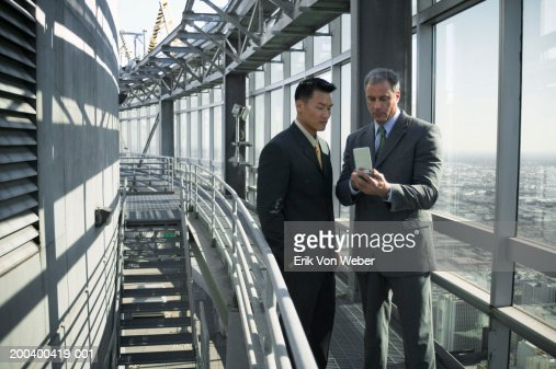 Businessmen talking and looking at organizer : Stock Photo