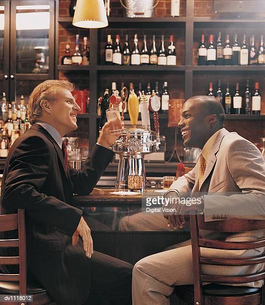 Businessmen Talking at a Bar