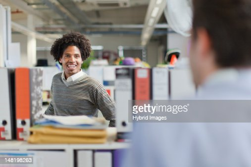 Businessmen talking at desks : Stock Photo
