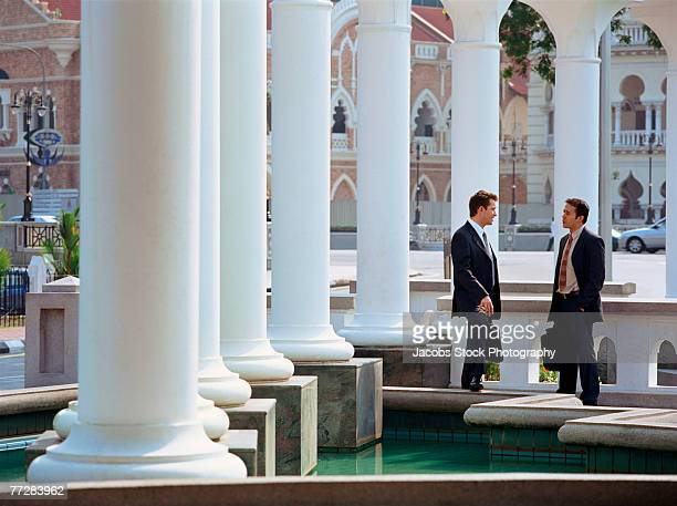Businessmen talking by fountain outdoors