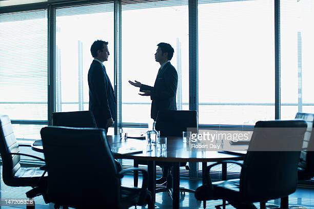 Businessmen talking face to face in conference room