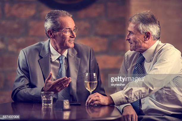 Businessmen talking in a bar.