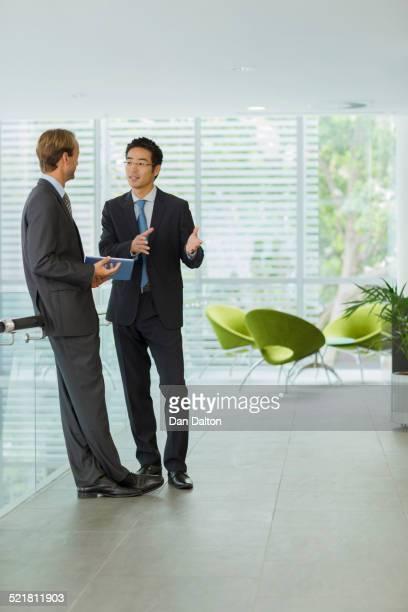 Businessmen talking in office building