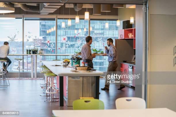 Businessmen talking in office kitchen