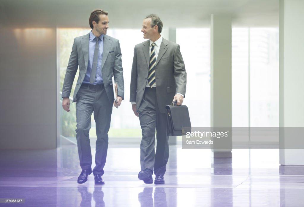 Businessmen talking in office lobby : Stock Photo