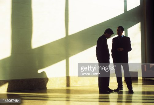 Businessmen talking in shadowed lobby : Stock Photo