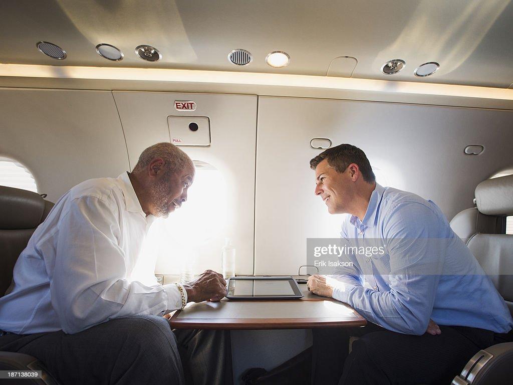Businessmen talking on airplane : Stock Photo