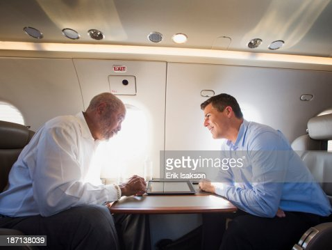 Businessmen talking on airplane