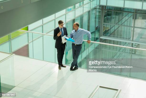 Businessmen talking on atrium balcony