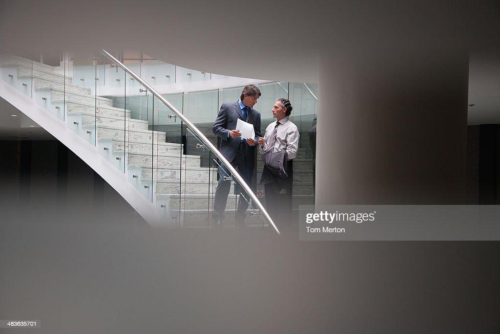 Businessmen talking on staircase : Stock Photo