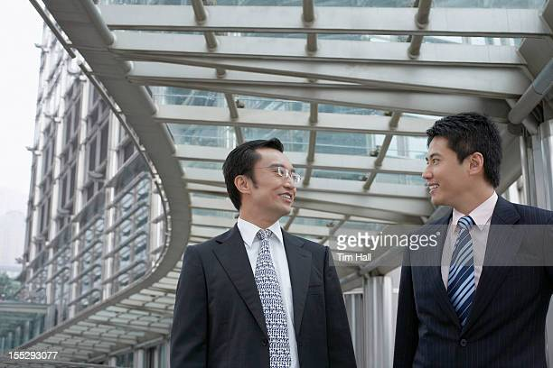 Businessmen talking on walkway