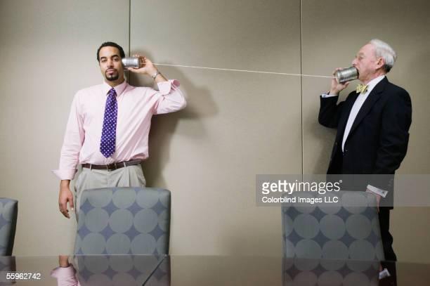 Businessmen talking through tin cans