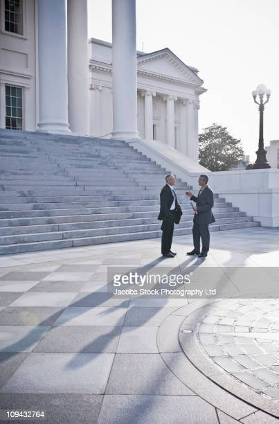 Businessmen talking together near steps