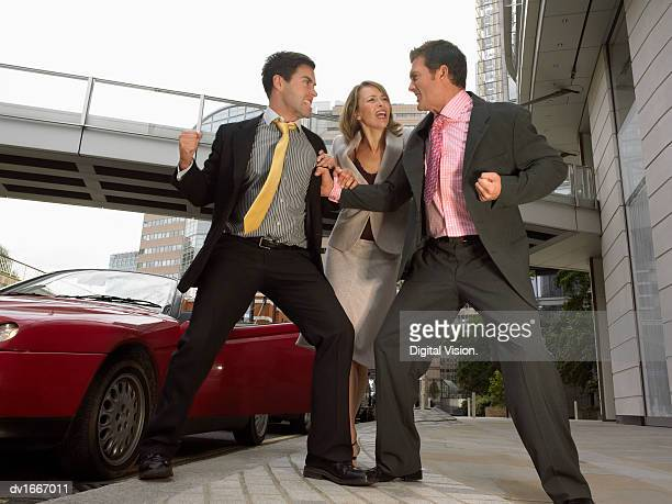 Businessmen Threatening One Another on the Street Near a Sports Car and a Businesswoman Trying to Stop Them