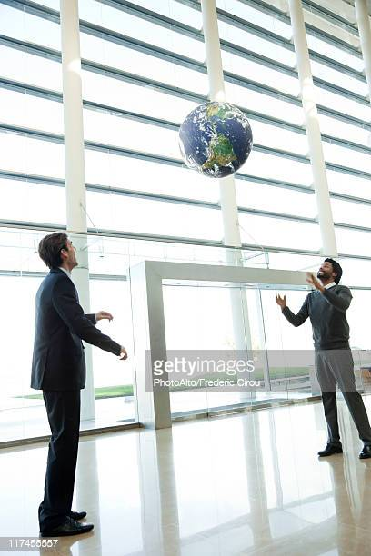 Businessmen throwing ball in lobby