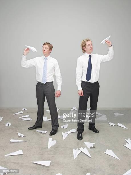 businessmen throwing paper aeroplanes
