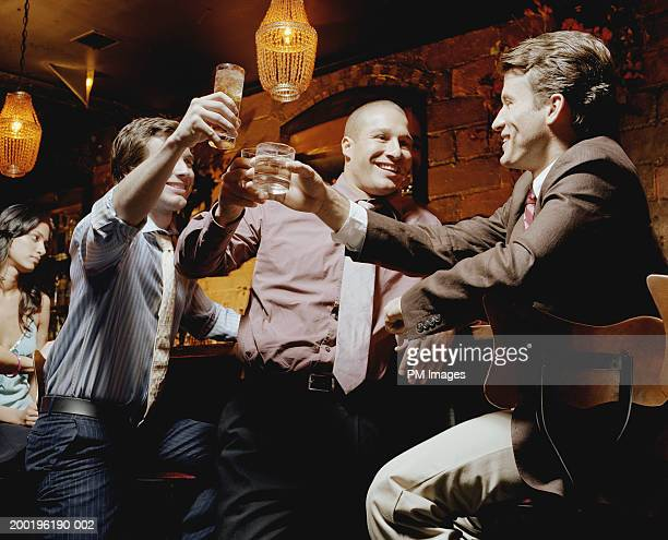 Businessmen toasting at bar