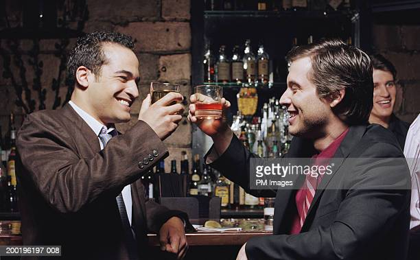 Businessmen toasting at bar, smiling