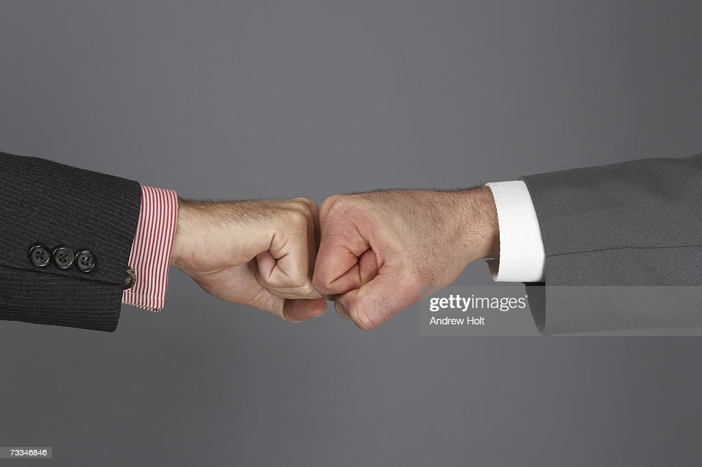 Businessmen touching knuckles together, close-up : Stock Photo